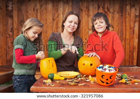 Family carving pumpkin lanterns for halloween - preparing the spooky accessories - stock photo