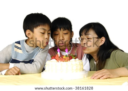 Family celebrating birthday- blowing out candles - stock photo