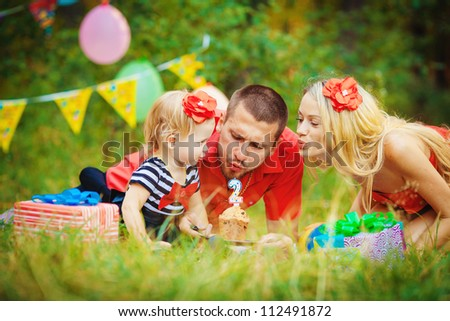Family celebrating birthday party in green park outdoors - stock photo