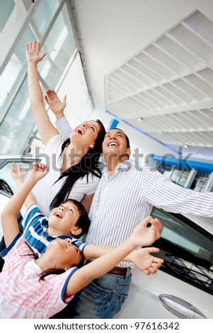 Family celebrating buying a new car with arms up - stock photo