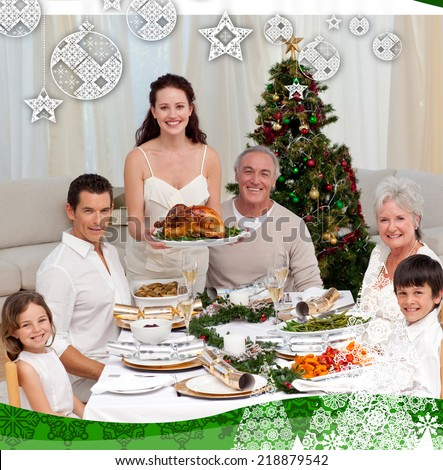 Family celebrating Christmas dinner with turkey against christmas themed frame - stock photo