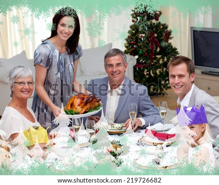 Family celebrating Christmas dinner with turkey against green snowflake design