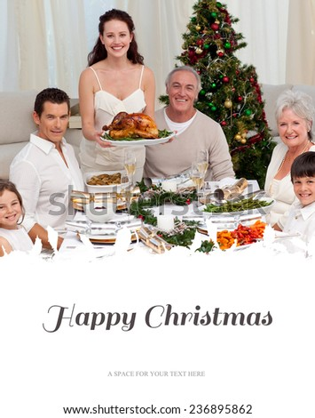 Family celebrating Christmas dinner with turkey against happy christmas
