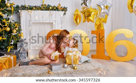 Family celebration of the New Year 2016. The mother kisses daughter near a Christmas tree. Giving gifts. Holiday and fun. - stock photo