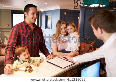 Family Checking In At Hotel Reception Desk - stock photo