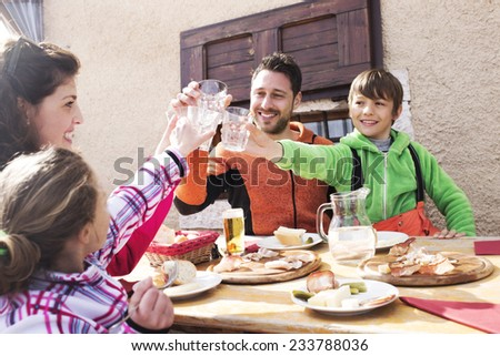 family cheers in a mountain chalet - stock photo