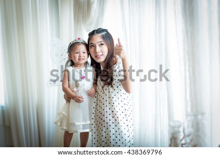 family, child and home concept - smiling parents and little girl  at home.Backlit shot - stock photo
