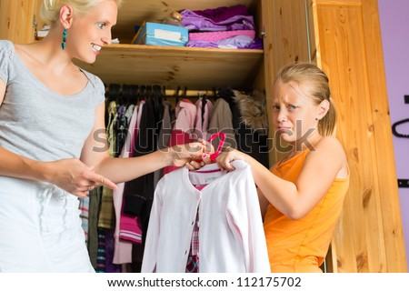 Family - child and mother in front of closet or wardrobe, teenager should put on a dress but does not like it - stock photo