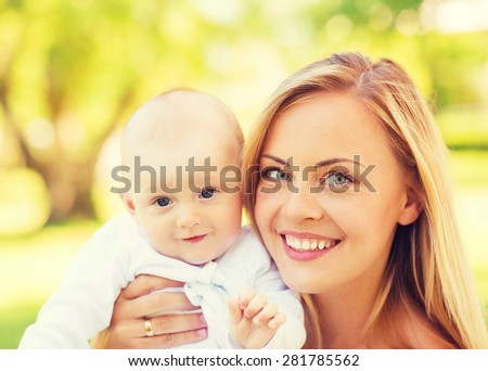 family, child and parenthood concept - close up of happy mother with little baby in park - stock photo
