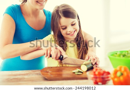 family, child, cooking and home concept - smiling little girl with mother chopping cucumber in the kitchen - stock photo