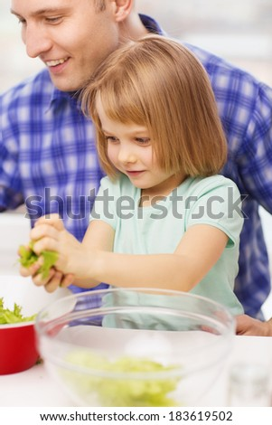 family, child, food and home concept - smiling father and little girl at kitchen cooking salad - stock photo