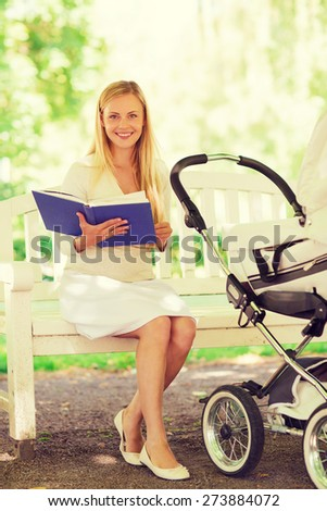 family, child, leisure, education and parenthood concept - happy mother with baby stroller reading book in park - stock photo