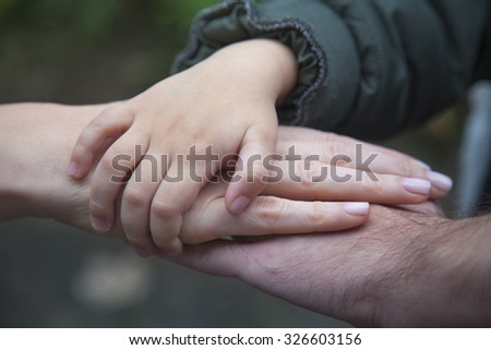 Family - child, mother and father holding hands in unity and supporting each other. - stock photo