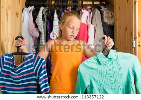 Family - child or teenager in front of her closet or wardrobe and looking for outfit - stock photo