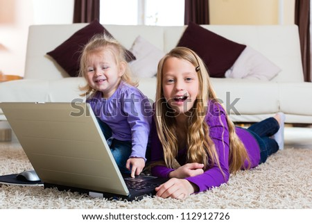 Family - child playing with the laptop lying on the floor, her little baby sister is with her - stock photo