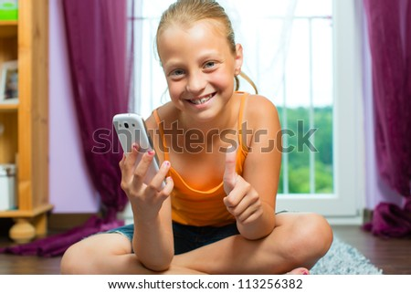 Family - child with cell or smartphone at home in the living room - stock photo
