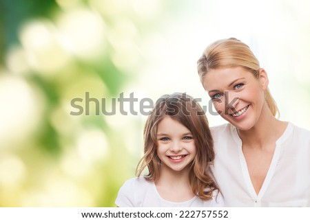 family, childhood, happiness, ecology and people - smiling mother and little girl over green background - stock photo