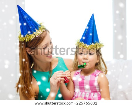 family, childhood, holidays and people concept - happy mother and daughter in blue party hats with party horns