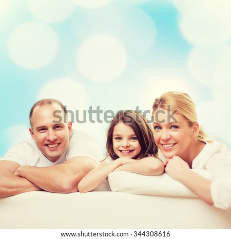 family, childhood, holidays and people - smiling mother, father and little girl over blue lights background - stock photo
