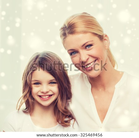 family, childhood, motherhood, people and happiness concept - smiling mother and little girl over snowflakes background - stock photo