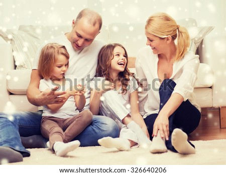 family, childhood, people and home concept - smiling parents with two little girls sitting on floor at home - stock photo
