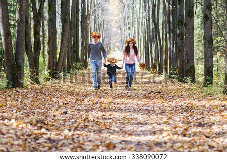 family, childhood, season  - happy family playing with autumn leaves in park. young family in autumn Park