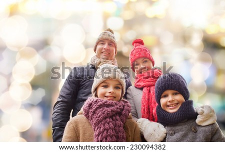 family, childhood, season, holidays and people concept - happy family in winter clothes over lights background - stock photo