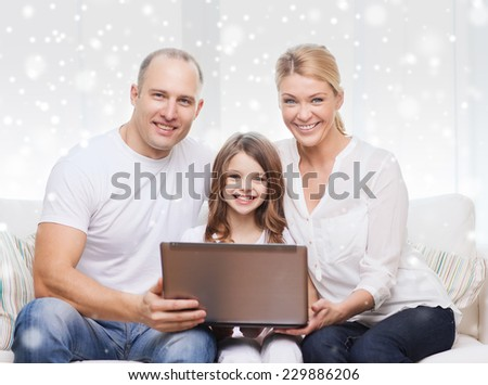 family, childhood, technology and people concept - smiling family with laptop computer over snowflakes background - stock photo