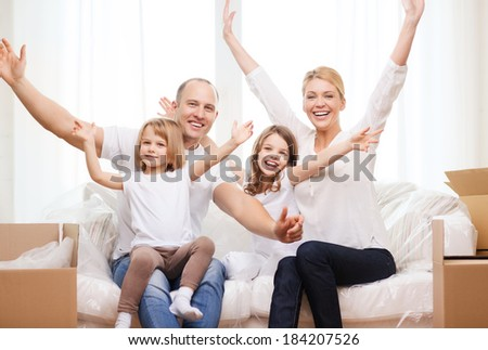 family, children, accommodation and home concept - smiling parents and two little girls waving hands at new home - stock photo