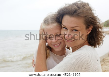 family. children and happy parent concept - hugging mother and daughter - stock photo