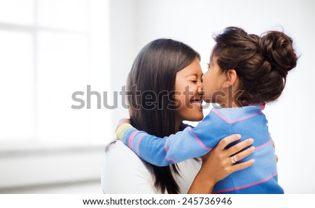 family, children and happy people concept - happy little girl hugging and kissing her mother over white room background - stock photo