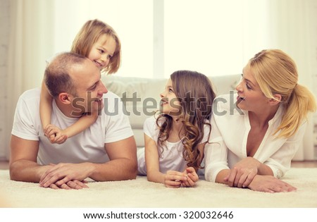 family, children and home concept - smiling family with and two little girls lying on floor at home - stock photo