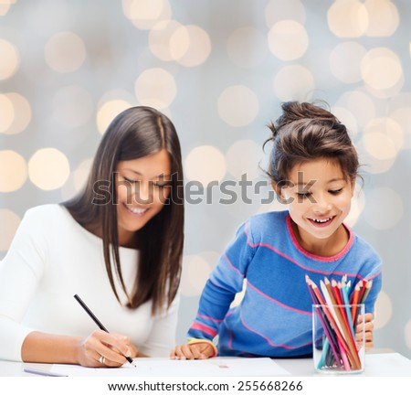 family, children and people concept - happy mother and daughter drawing over holidays lights background - stock photo