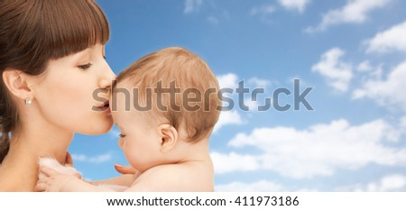 family, children and people concept - happy mother kissing baby boy over blue sky and clouds background - stock photo