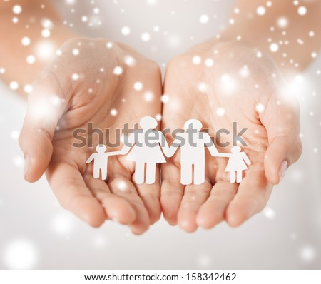 family, children, christmas, x-mas and happy people concept - woman cupped hands showing paper man family
