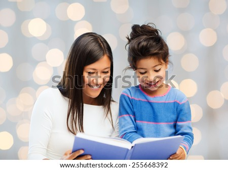 family, children, education and happy people concept - happy mother and little daughter reading book over holidays lights background - stock photo