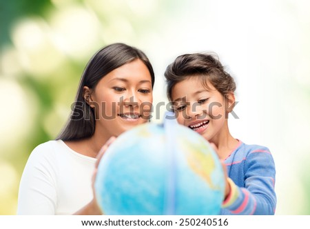 family, children, education, geography and people concept - happy mother and daughter with globe over green background - stock photo