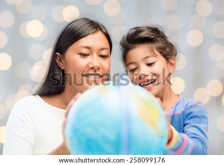 family, children, education, geography and people concept - happy mother and daughter with globe over holidays lights background - stock photo