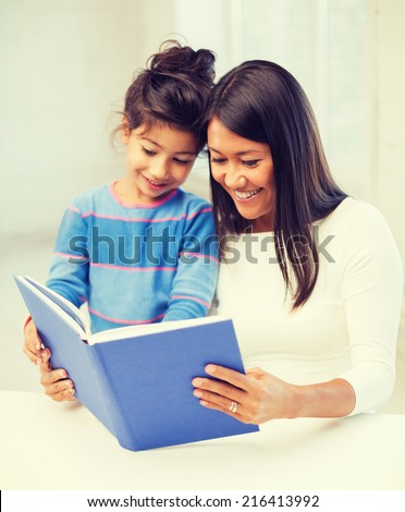 family, children, education, school and happy people concept - mother and daughter with book - stock photo