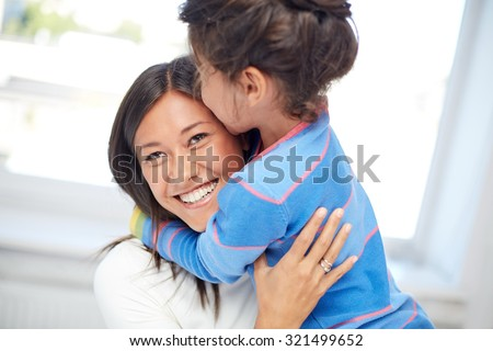 family, children, love and happy people concept - happy mother and daughter hugging at home - stock photo
