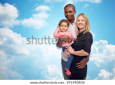 family, children, race and nationality concept - happy multiracial mother, father and little child over blue sky and clouds background - stock photo
