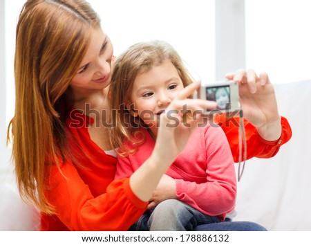 family, children, technology and happy people concept - smiling mother and daughter with digital camera - stock photo