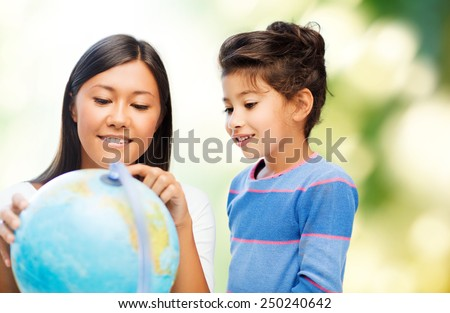 family, children, travel, geography and happy people concept - mother and daughter with globe over green background - stock photo