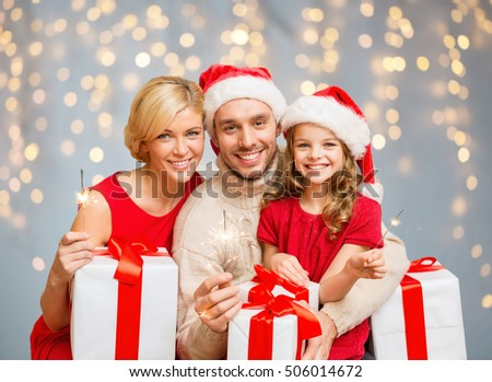 family, christmas and people concept - happy family in santa helper hats with many gift boxes and sparklers over lights background