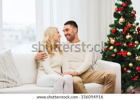 family, christmas, holidays, love and people concept - happy couple sitting on sofa at home