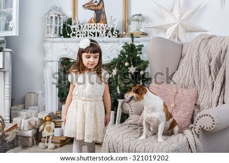 Family Christmas. Little girl and her best friend the dog look at each other. Christmas decorations home interior. A series of photos - stock photo