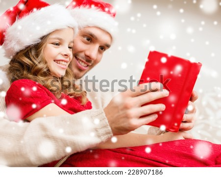 family, christmas, people and holidays concept - smiling father and girl in santa hats reading book or bible at home