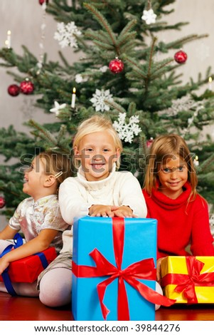 Family Christmas - three children having received gifts showing them around