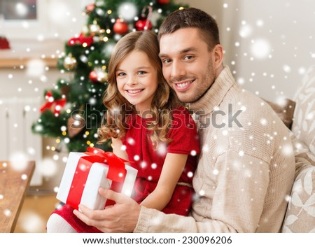family, christmas, winter holidays, childhood and people concept - smiling father and daughter holding gift box at home - stock photo