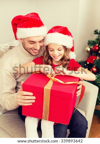 family, christmas, x-mas, winter, happiness and people concept - smiling father and daughter in santa helper hats opening gift box - stock photo